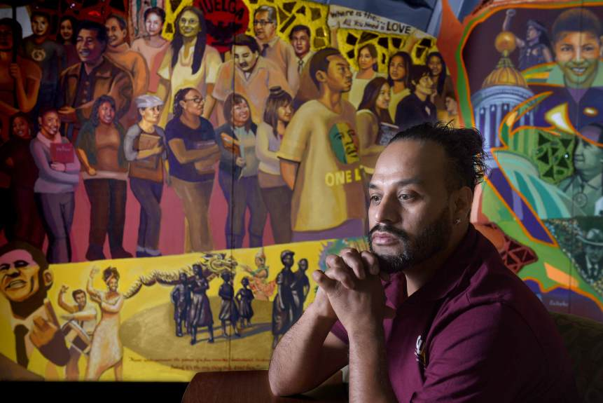 Cal State Dominguez Hills student Alejandro Campos Robledo has been having panic attacks since he learned he could lose his DACA status. Robledo often works through the stress with prayer and meditation. The mural behind him depicts the cultural diversity of the U.S. He fears he may get deported and have to leave his 11-year-old daughter behind. (Photo by Bill Alkofer, Contributing Photographer)